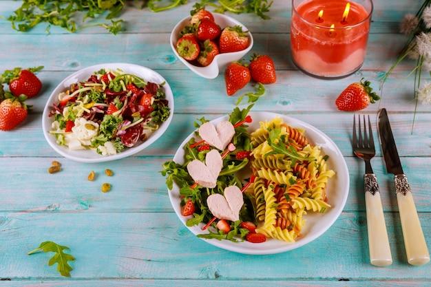 Salada com rúcula, macarrão rotini com cachorro-quente e morangos