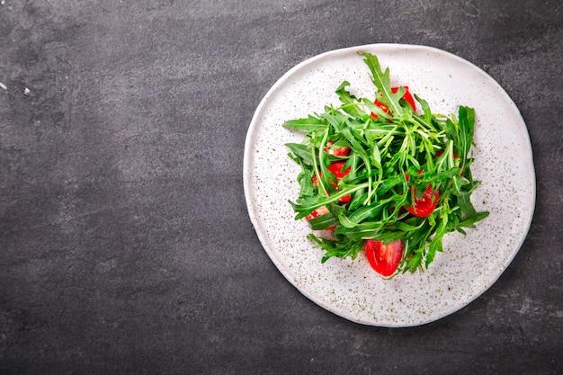 Salada com rúcula, tomate cereja fresco e azeite.