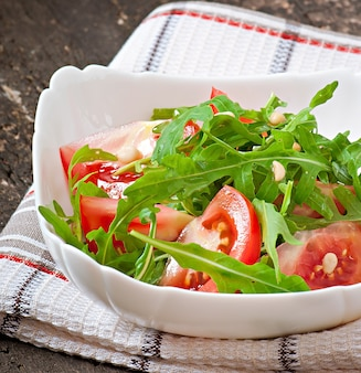 Salada com rúcula, tomate e pinhões