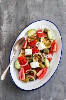 Salada com salada fresca e grelhada em prato branco sobre fundo de cerâmica