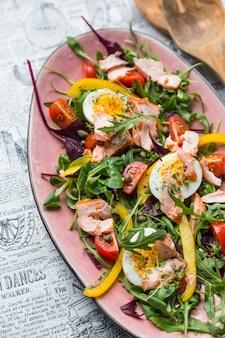 Salada com salmão e verdura em chapa rosa sobre fundo de jornal retrô