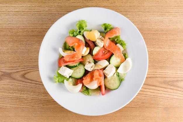 Salada com salmão, queijo feta, ovo, tomate, pepino, alface em prato branco sobre mesa de madeira leve