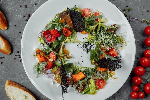 Salada com tomate abóbora e fígado frito. salada de halloween.