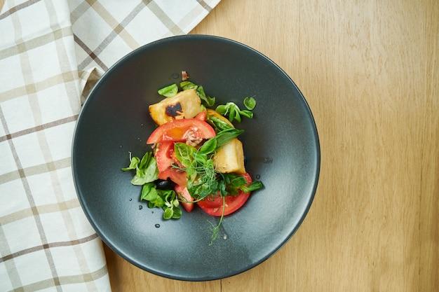 Salada com tomate cereja frito com queijo halumi e microgreen em tigela preta na mesa de madeira. comida de restaurante