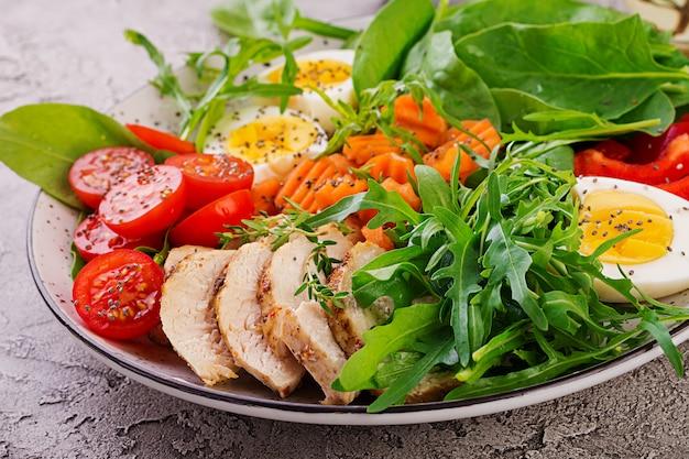 Salada com tomate cereja, peito de frango, ovos, cenoura, rúcula e espinafre