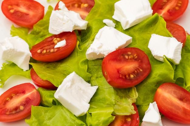 Salada com tomate cereja, queijo brynza macio e folhas de alface. prato dietético. fechar-se