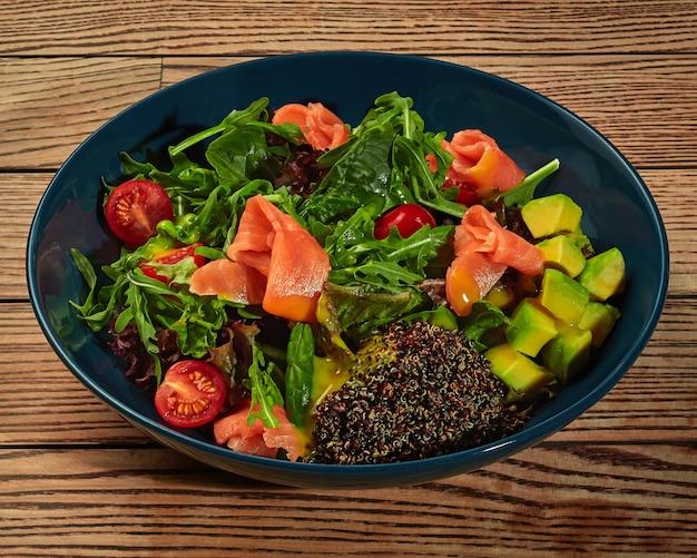 Salada com tomate cereja verde, abacate, salmão e sementes de quinua preta germinada