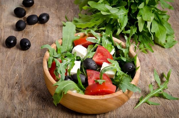 Salada com tomate e azeitonas em fundo de madeira