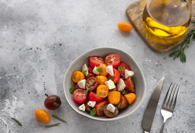 Salada com tomate fresco, queijo feta, manjericão, azeite superfície de concreto cinza conceito lanche saudável, cópia espaço, vista superior