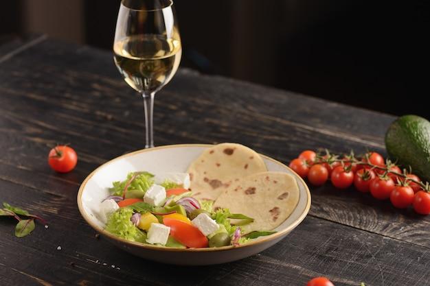 Salada com tomate, pepino, pimentão, azeitona e queijo feta. salada grega. em um prato de barro branco em uma mesa de madeira