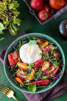 Salada com tomate, rúcula, queijo burrata e microgreens em um fundo de pedra verde, vista de cima, vertical