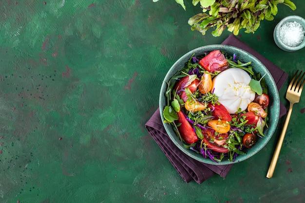 Salada com tomate, rúcula, queijo burrata e microgreens em um fundo de pedra verde, vista superior. copie o espaço