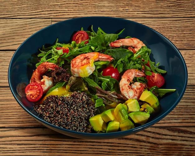 Salada com tomates cereja verdes, camarões abacate e sementes de quinua preta germinada