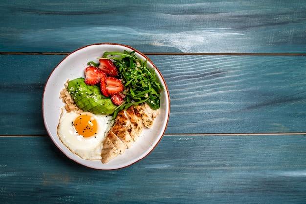 Salada da moda. tigela de buda vegan com salada de frango com rúcula e morangos. banner menu receita local para texto. vista do topo