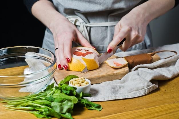 Salada da toranja do cozinheiro da mulher em uma placa de corte de madeira.