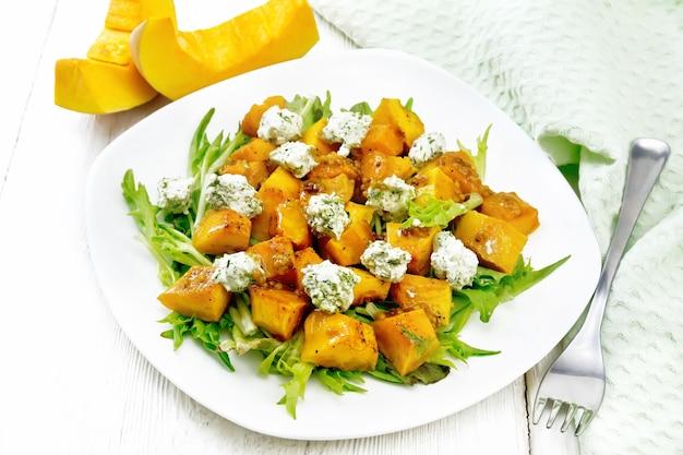 Salada de abóbora assada, rúcula com bolinhas de queijo salgado, temperada com mel, mostarda, alho e óleo vegetal em um prato, toalha e garfo