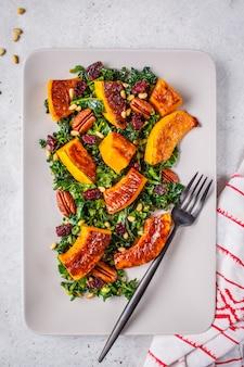 Salada de abóbora com nozes, cranberries e couve em uma placa retangular, vista superior.