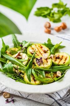 Salada de abobrinha grelhada com rúcula e nozes na chapa branca. conceito de comida saudável vegan.