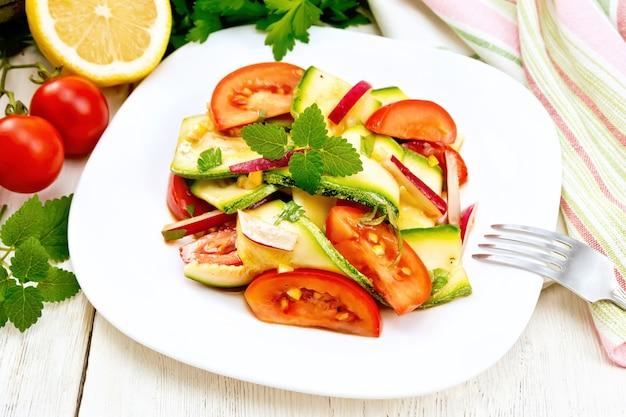 Salada de abobrinha jovem, rabanete, tomate e hortelã com suco de limão e molho de soja em um prato, guardanapo em um fundo de placa de madeira