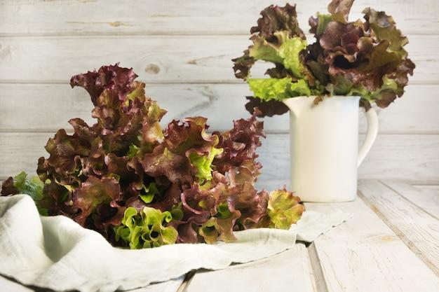 Salada de alface roxa fresca em madeira rústica branca