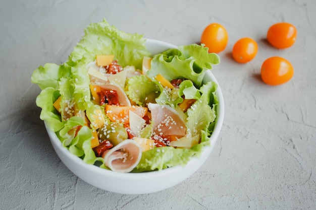 Salada de alface, tomate, azeitonas, tomate seco, presunto de parma, queijo cheddar