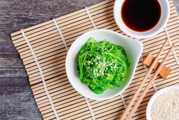 Salada de algas frescas com molho de soja e gergelim branco, comida vegetariana saudável. vista superior com espaço de cópia.