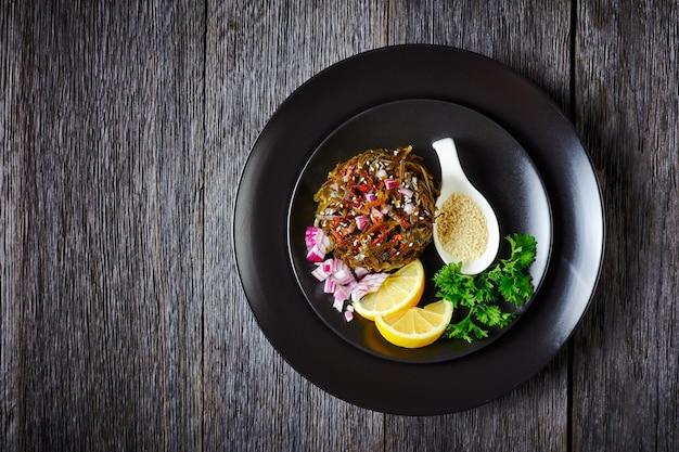 Salada de algas quentes de wakame em conserva, cebola roxa e rodelas de limão, em um prato preto com salsa fresca, polvilhada com sementes de gergelim, flocos de pimenta em cima de uma mesa de madeira, vista de cima, espaço de cópia