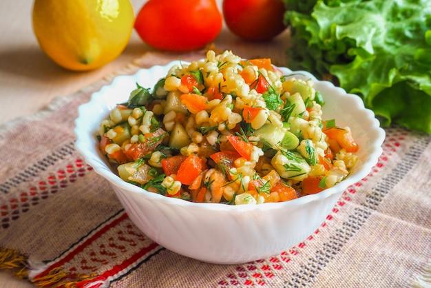 Salada de almoço fresco com legumes e bulgur. cozinha rústica simples e útil.