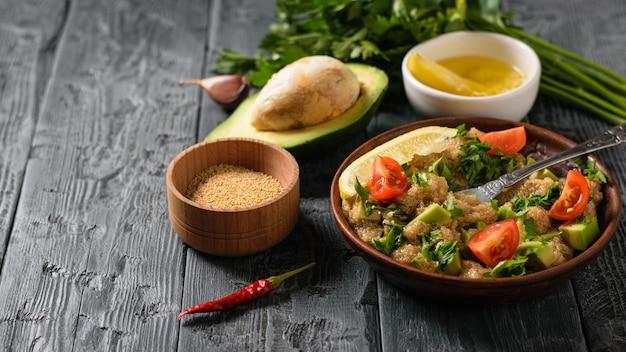 Salada de amaranto, abacate, pimenta, limão, salsa com sementes de tigela em uma mesa preta.
