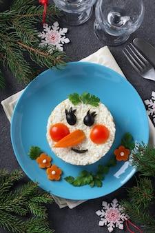 Salada de ano novo em forma de um boneco de neve em um prato azul sobre um fundo cinza. vista do topo