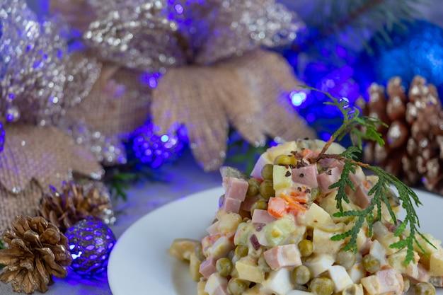 Salada de ano novo russo tradicional olivier servindo salada de natal com fundo de guirlanda azul