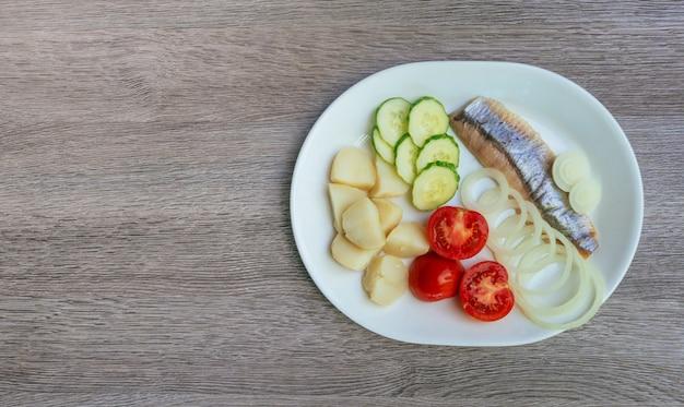 Salada de arenque com legumes na vista superior chapa branca