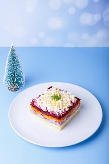 Salada de arenque sob um casaco de pele. salada russa tradicional em várias camadas de arenque, beterraba, batata, cenoura e ovos. close-up, fundo azul, árvore de natal em miniatura.