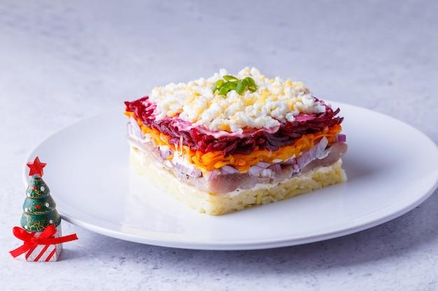 Salada de arenque sob um casaco de pele. salada russa tradicional em várias camadas de arenque, beterraba, batata, cenoura e ovos. close-up, plano de fundo cinza, árvore de natal em miniatura.