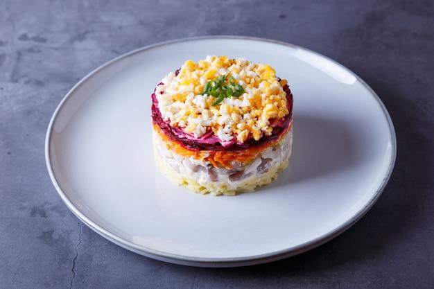 Salada de arenque sob um casaco de pele. salada russa tradicional em várias camadas de arenque, beterraba, batata, cenoura e ovos. close-up, plano de fundo cinza.