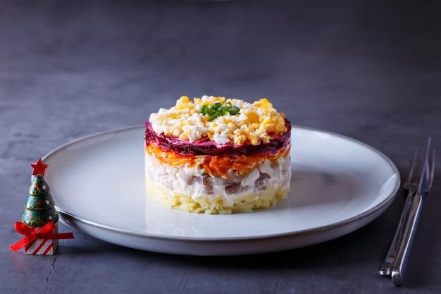 Salada de arenque sob um casaco de pele salada tradicional russa em várias camadas de batatas de beterraba de arenque