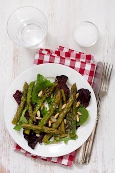 Salada de aspargos e pinhões em chapa branca com copo de água