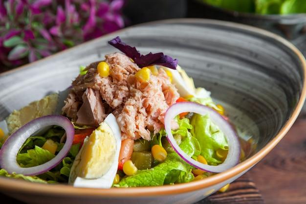 Salada de atum close-up com alface, ovos, tomate, pepino, cebola e milho em uma mesa de madeira escura horizontal