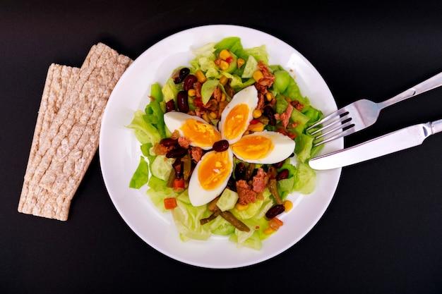 Salada de atum com alface, ovos e tomates com pães na tabela preta.