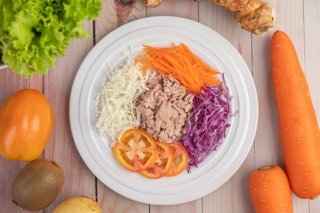 Salada de atum com cenoura, tomate, couve em um prato branco sobre um piso de madeira.