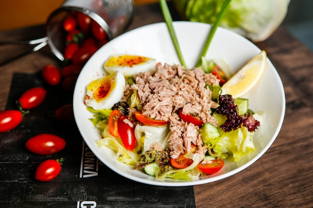 Salada de atum com tomate e ovo cozido em um prato com limão.