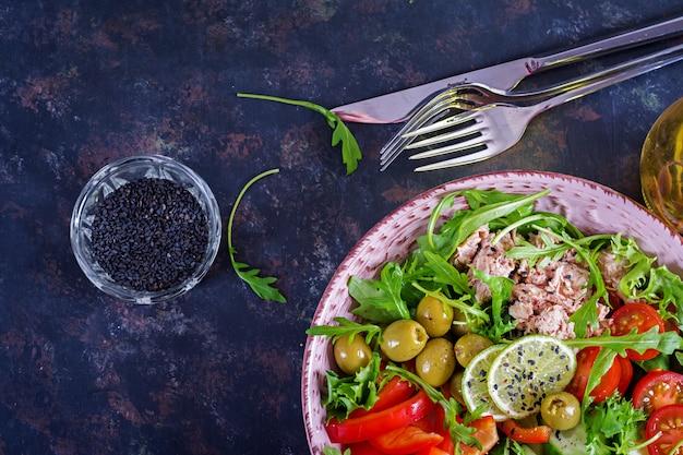 Salada de atum com tomates, azeitonas, pepino, pimentão e rúcula no fundo rústico