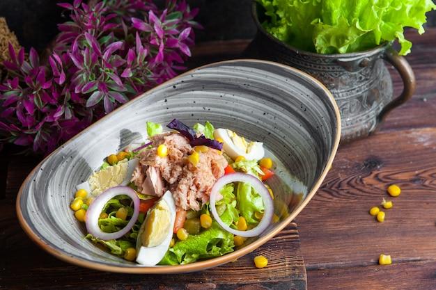 Salada de atum de vista lateral com alface, ovos, tomate, pepino, cebola e milho em uma mesa de madeira escura horizontal