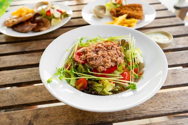 Salada de atum em um prato sobre uma mesa em um café de verão