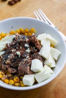 Salada de atum em uma mesa marrom com uma cebola de queijo garfo prateado