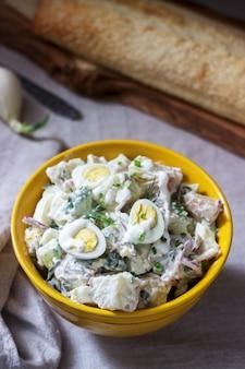 Salada de batata americana tradicional com ovo e maionese, servida com pão. estilo rústico.