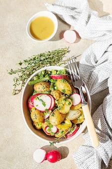Salada de batata caseira com feijão verde, rabanete fresco e molho de ervas com azeite e molho de mostarda.