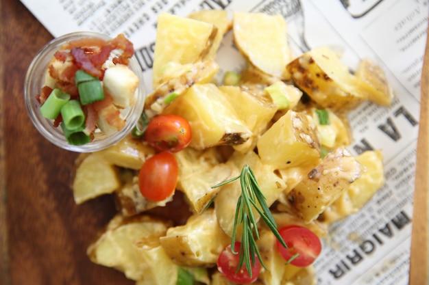 Salada de batata em fundo de madeira