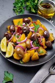 Salada de batata quente com azeitonas, pimenta, salsa e cebola roxa em um prato de cerâmica preta na superfície de concreto escuro