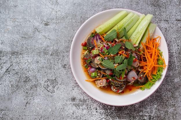 Salada de berbigão apimentada em fundo escuro